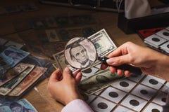 Cinque dollari nella mano del ` s della donna, tramite una lente d'ingrandimento Immagine Stock Libera da Diritti