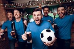 Cinque fan di calcio che bevono birra che celebra e che incoraggia alla barra di sport fotografie stock libere da diritti