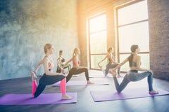 Cinque giovani signore esili di yoga stanno facendo l'allungamento dell'esercizio su Th Fotografia Stock Libera da Diritti