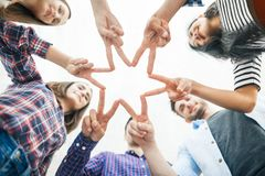 Cinque giovani sorridenti fanno la forma della stella dalle dita Fotografie Stock Libere da Diritti