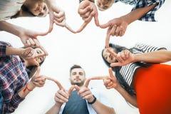 Cinque giovani sorridenti fanno la forma della stella dalle dita Fotografie Stock