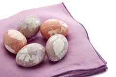 Cinque hanno dipinto le uova di Pasqua sul tovagliolo viola del tessuto sopra bianco Fotografia Stock