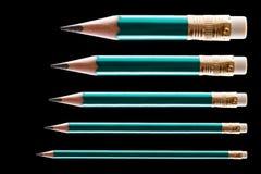 Cinque matite sul nero fotografia stock