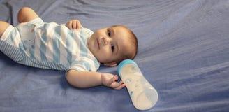 Cinque mesi del neonato che gioca sul letto fotografie stock libere da diritti
