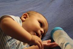 Cinque mesi del neonato che gioca sul letto Fotografia Stock