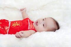 Cinque mesi svegli di bambino asiatico che sorride nel cheongsam rosso Fotografia Stock