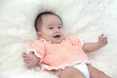 Cinque mesi svegli di bambino asiatico nella risata arancio del vestito Immagine Stock