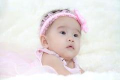 Cinque mesi svegli di bambino asiatico in vestito rosa , su carpe molle Fotografie Stock