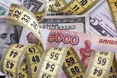 Cinque mila rubli con la misura di nastro sulle banconote del dollaro Fotografia Stock