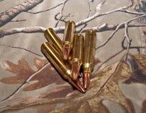 Cinque pallottole del fucile con un fondo di camo Fotografia Stock Libera da Diritti