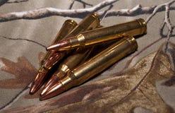 Cinque pallottole del fucile con un fondo di camo Fotografie Stock Libere da Diritti