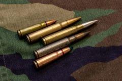 Cinque pallottole del fucile sul cappotto militare del cammuffamento a fondo fotografia stock