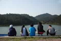 Cinque persone si siedono vicino al lago in montagne fotografia stock libera da diritti