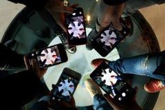 Cinque persone stanno prendendo la foto delle loro gambe sul pavimento di vetro fotografie stock