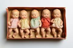 Cinque piccole bambole in una scatola, retro giocattoli Immagine Stock