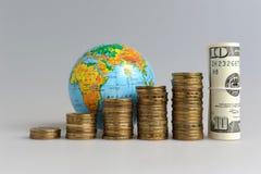 Cinque pile di monete con un globo e un pacco dei dollari Fotografie Stock Libere da Diritti