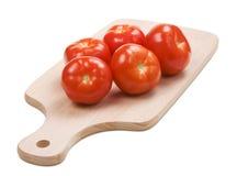 Cinque pomodori rossi freschi sulla scheda di taglio Fotografia Stock