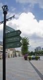 Cinque Roadsigns sotto il cielo nuvoloso nella città Fotografie Stock Libere da Diritti