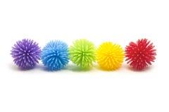 Cinque sfere variopinte di Stess Koosh in una riga Fotografie Stock