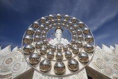 Cinque statue bianche di Buddha che si siedono allineamento buono davanti a cielo blu e che decorano specchio attraente meravigli Fotografie Stock Libere da Diritti