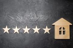 Cinque stelle e una casa di legno su un fondo concreto grigio Il concetto di migliore alloggio, classe di lusso degli appartament Fotografia Stock Libera da Diritti