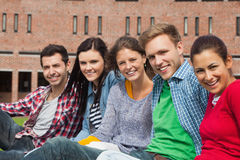 Cinque studenti che si siedono sull'erba che sorride alla macchina fotografica Immagine Stock Libera da Diritti