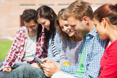 Cinque studenti sorridenti che si siedono sull'erba facendo uso della compressa Fotografie Stock