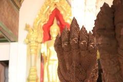 Cinque teste del Naga o del drago dello stucco con fuori mettono a fuoco la statua d'ottone di Buddha immagine stock