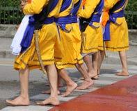 Cinque uomini con i vestiti lunghi che camminano a piedi nudi tramite le vie Immagine Stock