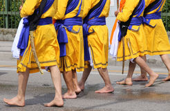 Cinque uomini con i vestiti lunghi che camminano a piedi nudi tramite le vie Immagini Stock Libere da Diritti