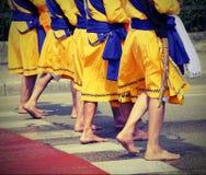 Cinque uomini della religione sikh con i vestiti lunghi che camminano a piedi nudi Immagine Stock Libera da Diritti