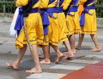 Cinque uomini della religione sikh con i vestiti lunghi che camminano a piedi nudi Fotografie Stock