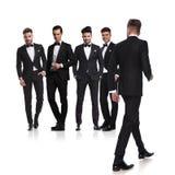 Cinque uomini si sono vestiti nei tuxedoes con il capo che cammina indietro immagine stock