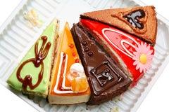 Cinque varie parti della torta su un cassetto Fotografia Stock
