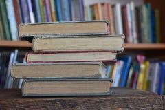 Cinque vecchi libri in una biblioteca Immagini Stock
