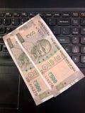 Cinquecento rupie di note indiane di valuta su una tastiera del computer portatile fotografie stock libere da diritti