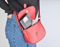 Cinta audio y de video de 80s en un women& rojo x27; bolso de s Un bolso de moda cuelga en el hombro de una chica joven atractiva Fotos de archivo libres de regalías