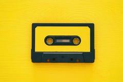 Cinta de casete retra sobre la tabla de madera amarilla Visión superior imágenes de archivo libres de regalías