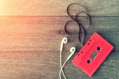 Cinta de casete roja con el auricular sobre la tabla de madera Visión superior Enríe Fotos de archivo
