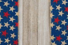 Cinta de la arpillera de las estrellas rojas y azules en fondo de madera resistido Imagen de archivo libre de regalías