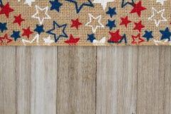 Cinta de la arpillera de las estrellas rojas, blancas y azules en backgr de madera resistido fotos de archivo