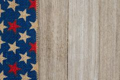 Cinta de la arpillera de las estrellas rojas, blancas y azules en backgr de madera resistido Foto de archivo