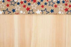 Cinta de la arpillera de las estrellas rojas, blancas y azules en el fondo de madera Imagenes de archivo