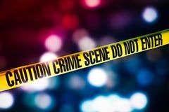 Cinta de la escena del crimen con las luces rojas y azules en el fondo Foto de archivo libre de regalías