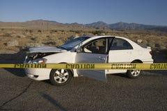 Cinta de la precaución con el coche dañado Foto de archivo