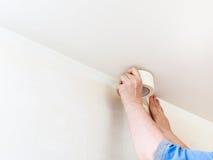 Cinta de los arreglos del decorador en la pared antes de pintar fotos de archivo