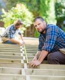 Cinta de Measuring Wood With del carpintero mientras que compañero de trabajo imagen de archivo libre de regalías