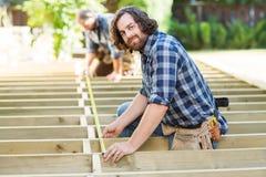 Cinta de Measuring Wood With del carpintero mientras que compañero de trabajo fotografía de archivo