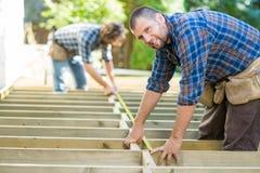 Cinta de Measuring Wood With del carpintero mientras que compañero de trabajo fotos de archivo libres de regalías