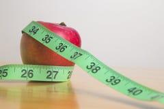 Cinta de medición alrededor de una manzana Imagen de archivo libre de regalías
